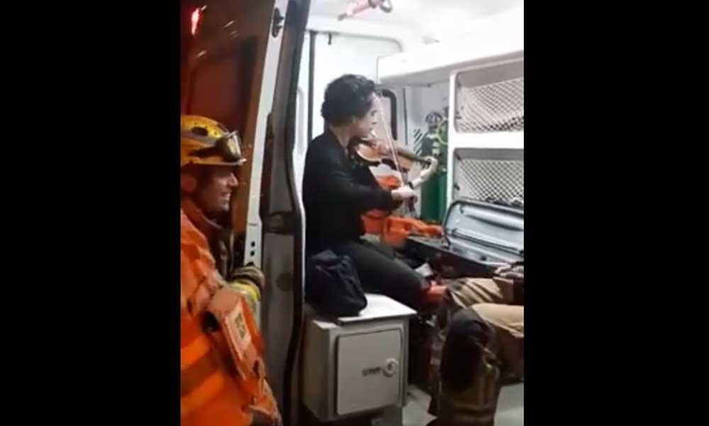 Vídeo: após capotar veículo, mulher toca violino para bombeiros